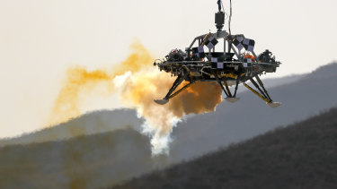 A lander is lifted during a test of hovering, obstacle avoidance and deceleration capabilities of a Mars lander at a facility in Huailai in China's Hebei province.