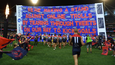 The Demons run through their banner on Friday night.