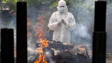 A relative in protective suit performs  rituals near the body of a loved one. during cremation in Gauhati, India.
