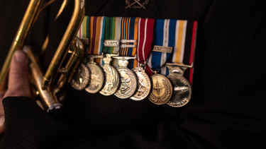 Afghanistan war veteran Duncan Clements displays his medals as he plays the bugle at  Parkes War Memorial.