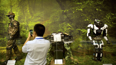 A visitor takes a photo of a display of robotic military technology at an exhibition highlighting China's achievements under five years of leadership by Chinese President Xi Jinping.