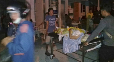 A patient is evacuated from a hospital after the earthquake hit Poso on the island of Sulawesi on Friday.