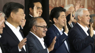 From left, Chinese President Xi Jinping, Papua New Guinea's Prime Minister Peter O'Neill, Japanese Prime Minister Shinzo Abe, and U.S. Vice President Mike Pence wave as they pose for a group photo at APEC Haus in Port Moresby, Papua New Guinea.