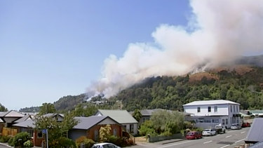 Smoke rises from a busfire coming over the ridge behind a residential area in Wakefield, New Zealand, on Friday.