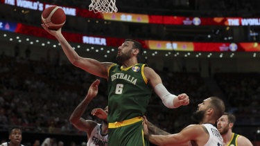 Andrew Bogut of Australia puts up a shot over Amath M'Baye, left, and Evan Fournier of France.