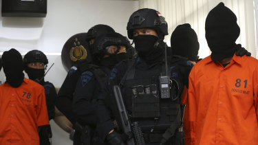 Indonesian Special Detachment 88 anti-terror police unit escorts terror suspects during a press conference at in Jakarta on Friday.