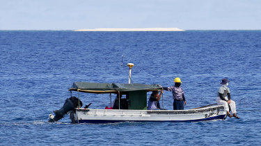 Engineers from the Philippine government survey the area around the Philippine-claimed Thitu Island in the disputed South China Sea.