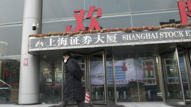 A security officer wearing a face mask walks in front of the Shanghai Stock Exchange building in Shanghai on Monday. The benchmark index dived almost 9 per cent as it re-opened after a 10-day break for Chinese New Year.