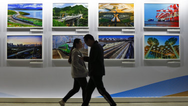 People walk by a display board showcasing China's construction projects at the media centre of the Belt and Road Forum in Beijing.