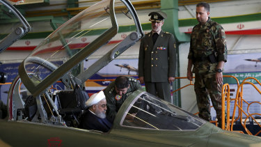 Iranian President Hassan Rouhani is briefed by an air force pilot as he sits in the cockpit of a fighter jet, before an inauguration ceremony of the aircraft in Iran last week.