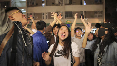 Pro-democracy supporters celebrate after pro-Beijing politician Junius Ho lost his election in Hong Kong.