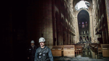 A man walks inside the damaged Notre-Dame Cathedral on Tuesday.