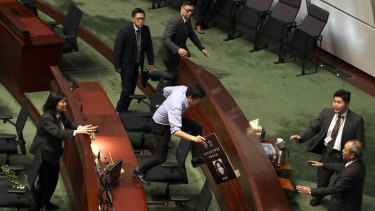 Politician Au Nok-hin leaps across desks to chase Carrie Lam in the Legislative Council in Hong Kong on Thursday.