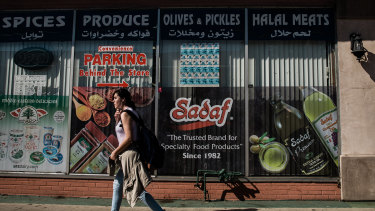 A young woman passes by a Middle Eastern market on Main Street in El Cajon, California.