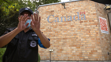 A security officer wearing a face mask to help protect against the coronavirus gestures outside the Canadian embassy in Beijing on Thursday.