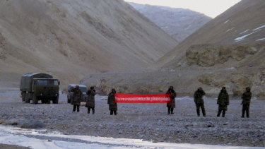 "Chinese troops hold a banner which reads ""You've crossed the border, please go back"" in Ladakh, India, in 2013."