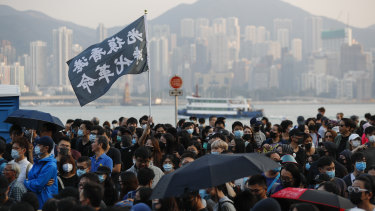 "Protesters wave a flag reading ""Liberate Hong Kong, the Revolution of Our Times"" during the march on Sunday."