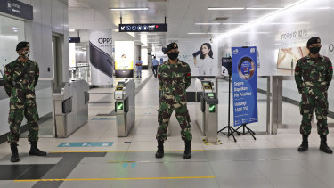 Soldiers stand guard at an MRT station in Jakarta, Indonesia.