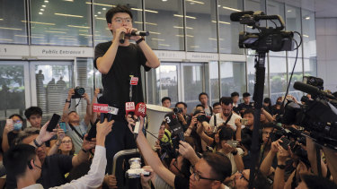 Pro-democracy activist Joshua Wong speaks to protesters near the Legislative Council in Hong Kong on Monday.