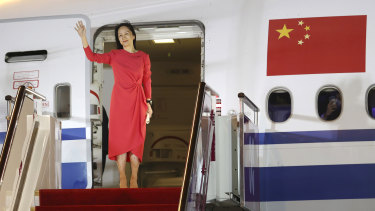 Meng Wanzhou waves as she steps out of an airplane in Shenzhen.