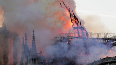 The spire collapses as flames burn the roof of the Notre-Dame Cathedral.