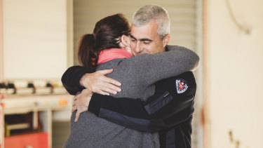 Tim Wimborne and Alanna Davis embrace on Saturday. Mr Wimborne stayed with Ms Davis while the fire crew rescued TJ.