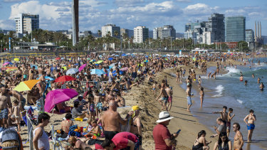"""People enjoy the warm weather on the beach in Barcelona. Spanish government has announced that the north-western region of Galicia will move next week to what the government calls """"the new normal""""."""