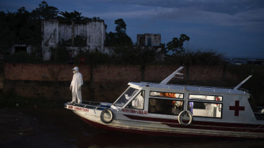 A health worker stands on a boat carrying COVID-19 patient Jose da Conceição as he waits for an ambulance to transfer him to a hospital after arriving in the port of Manacapuru, Amazonas state, Brazil.