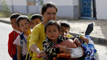 A Uighur woman and children sit on a motor-tricycle after school at the Unity New Village in Hotan, in western China's Xinjiang region. Birth rates in the mostly Uighur regions of Hotan and Kashgar have plunged  since 2015.