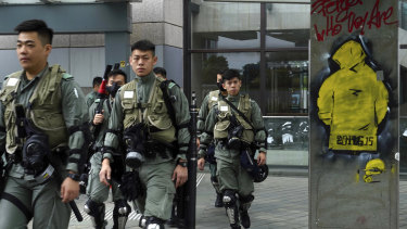 Riot policemen patrol near the government headquarters in Hong Kong on Tuesday.