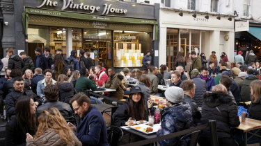 Customers dine in an outdoor seating area of a restaurant in Soho in London.