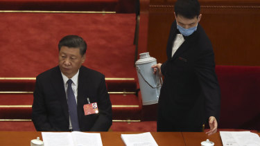 An attendant wearing a face mask to protect against the new coronavirus refills a cup next to Chinese President Xi Jinping.