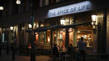 Customers sit in an outside area of a bar in Soho in London.