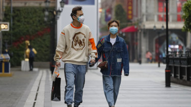 A couple wearing protective masks to prevent the new coronavirus outbreak walk on a re-opened commercial street in Wuhan.