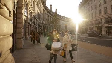 Pedestrians carrying shopping bags walk along Regents Street in London.