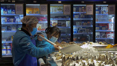 Workers shovel ice onto imported seafood at a Beijing supermarket.