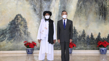 In July, Taliban co-founder Mullah Abdul Ghani Baradar, left, and Chinese Foreign Minister Wang Yi pose for a photo during their meeting in Tianjin, China.