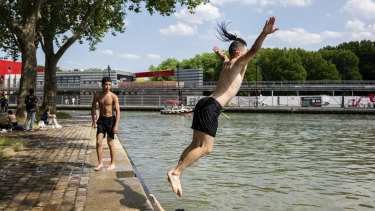 Young French people dive in the Canal de l'Ourcq in Paris.