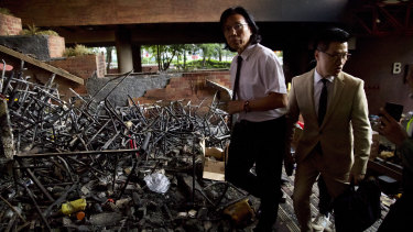 Gary Fan Kwok-wai, newly elected district councillor, right, and lawyer Wong Kwok Tung, left, walk through burnt debris as they try to meet with the last of trapped protesters at the Polytechnic University in Hong Kong on Monday.