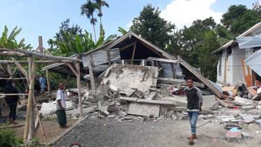 Villagers walk near destroyed homes in Lombok.