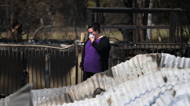 Naomi Elwell inspects the remains of her mother's house, which was destroyed by bushfires.