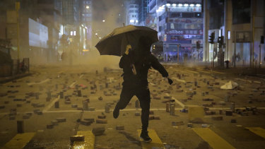 A protester with an umbrella runs away from tear gas fired by riot police on a street scattered with bricks during a protest in Hong Kong late last year.