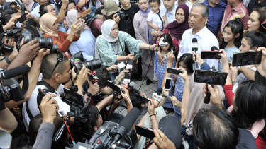 Muhyiddin Yassin, second in white shirt, talks to the media after being appointed as new prime minister.