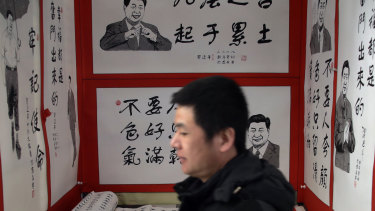 A man walks by posters featuring drawings of Chinese President Xi Jinping and his quotes, on display for sale at a market in Beijing.