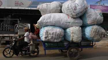 A couple transports sacks loaded with scrap materials into Phnom Penh, Cambodia