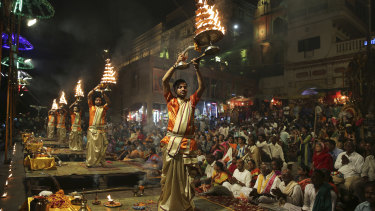 Devotees and tourists watch as Hindu priests perform daily rituals in reverence for river Ganges on its banks, in Varanasi, India, in March.