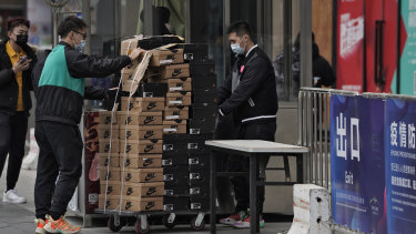 Workers push a cart loaded with Nike shoes past a security post at a shopping mall in Beijing last week.