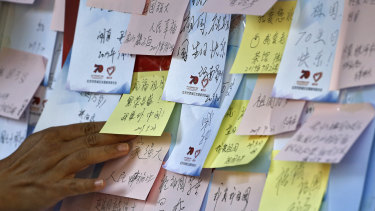 A woman places her note on a board near Tiananmen Square where visitors have been writing their wishes for the motherland ahead of the celebrations.