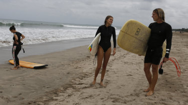Foreign tourists carry their surf board at Kuta beach, Bali, after a three-month virus lockdown lifted, allowing local people and stranded foreign tourists to resume public activities before foreign arrivals resume in September.