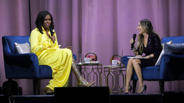 Former first lady Michelle Obama, left, is interviewed by Sarah Jessica Parker during an appearance for her book, Becoming.